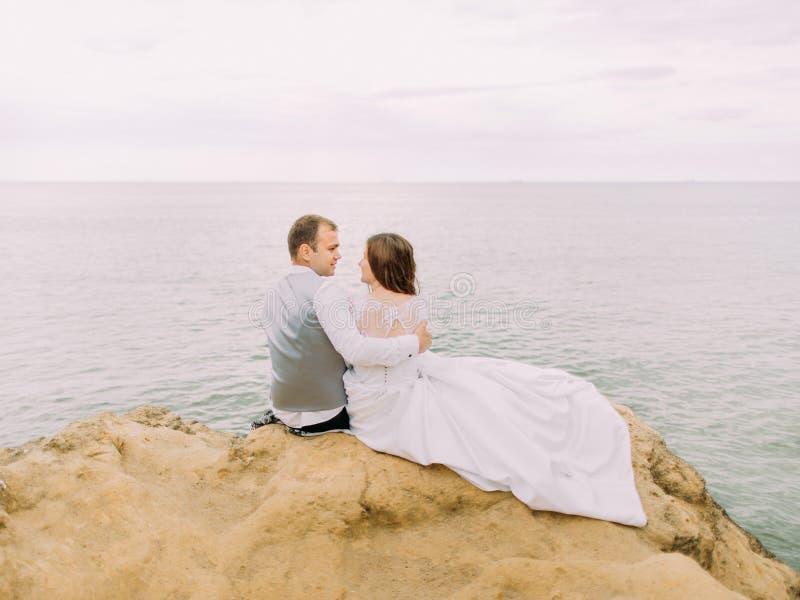 Romantikerbaksidasikt av det rättvisa gifta sammanträdet på klippan bland havet under solnedgången arkivbilder