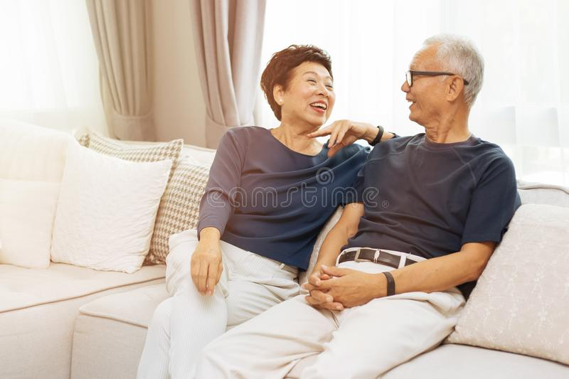 RomantiRomantic senior Asian couple laughing and sitting on sofa at home. stock images