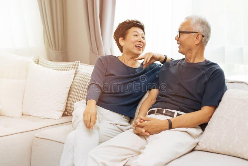 RomantiRomantic starsza Azjatycka para śmia się w domu i siedzi na kanapie obrazy stock