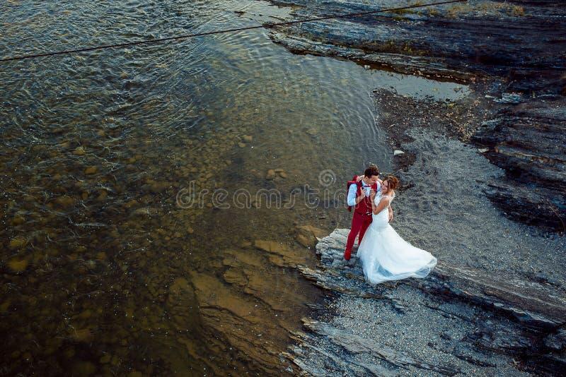 Romantisch über Porträt der lächelnden Jungvermählten, die zart in der Flussbank während des sonnigen Tages umarmen stockfotos