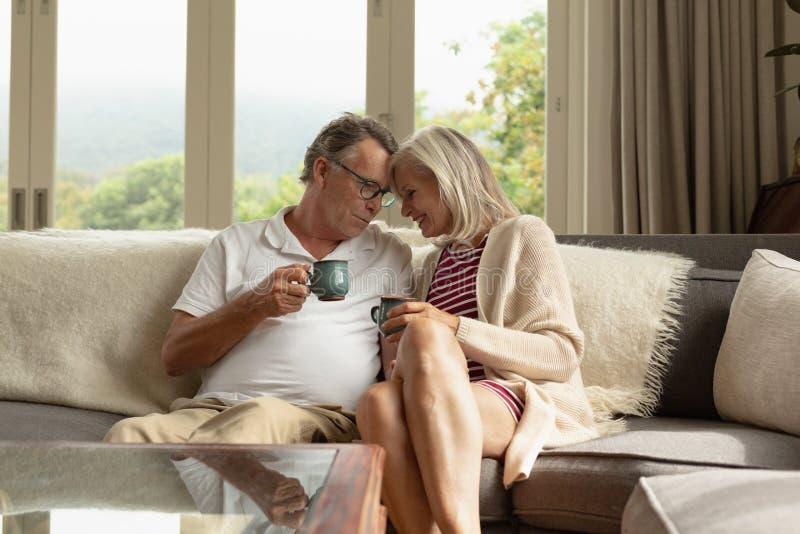 Romantisch actief hoger paar die koffie op bank in een comfortabel huis hebben stock afbeeldingen