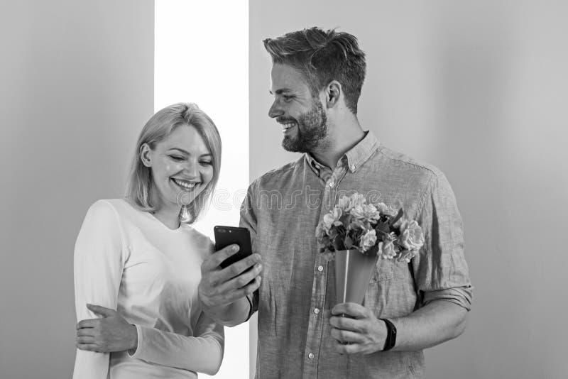 Romantisch concept Paar in liefde interessant telefonisch Kerel met telefoon en boeket van bloemen, pastelkleurroze en groen royalty-vrije stock fotografie