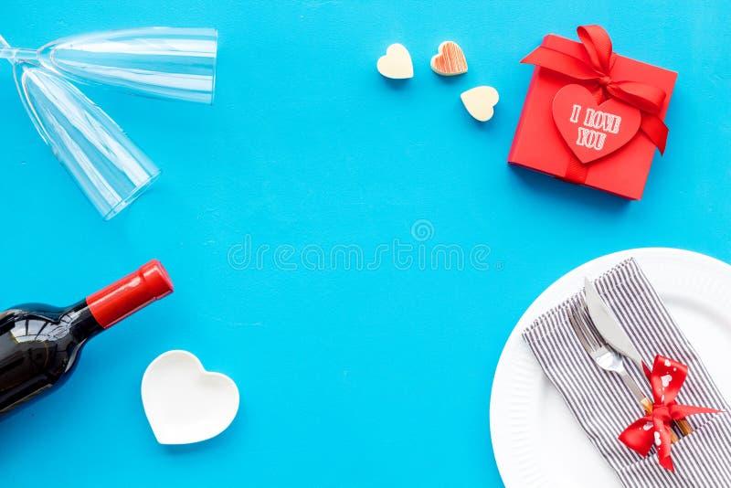 Romantisch diner op de Dag van Valentine Verfraaide schotels, vaatwerk, wijn en giftdoos op blauwe achtergrond hoogste meningscop stock foto