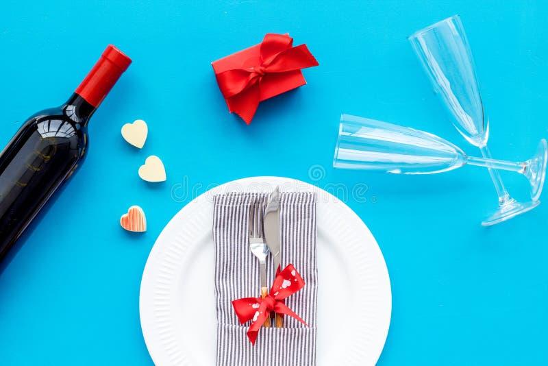 Romantisch diner op de Dag van Valentine Verfraaide schotels, vaatwerk, wijn en giftdoos op blauwe hoogste mening als achtergrond royalty-vrije stock afbeelding