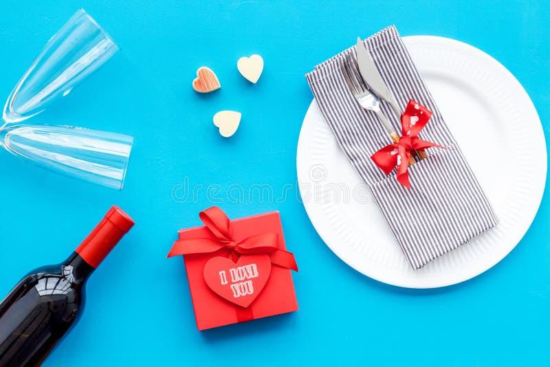 Romantisch diner op de Dag van Valentine Verfraaide schotels, vaatwerk, wijn en giftdoos op blauwe hoogste mening als achtergrond royalty-vrije stock fotografie