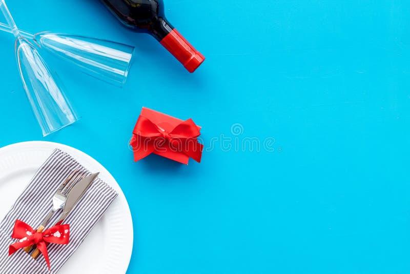Romantisch diner op de Dag van Valentine Verfraaide schotels, vaatwerk, wijn en giftdoos op blauwe hoogste mening als achtergrond stock fotografie