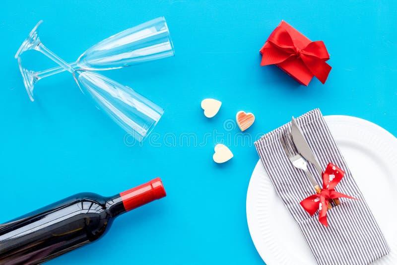 Romantisch diner op de Dag van Valentine Verfraaide schotels, vaatwerk, wijn en giftdoos op blauwe hoogste mening als achtergrond stock afbeeldingen
