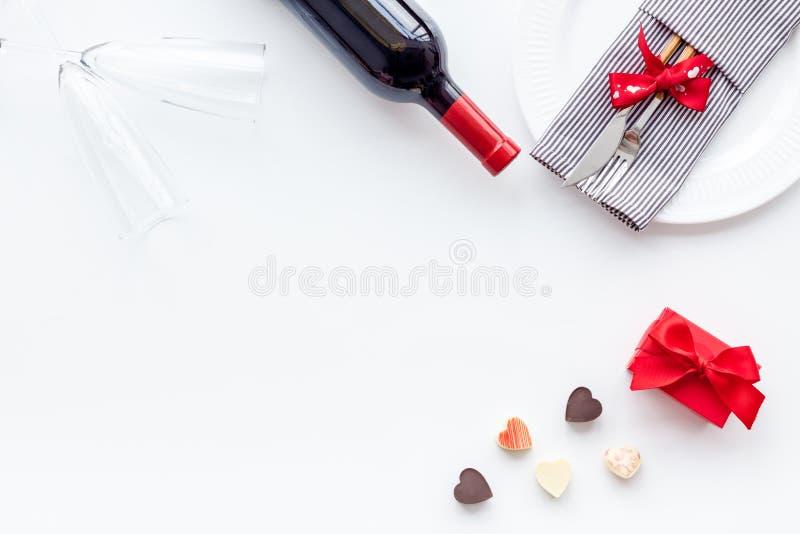 Romantisch diner op de Dag van Valentine Verfraaide schotels, vaatwerk, wijn en giftdoos op witte achtergrond hoogste meningsruim stock afbeelding