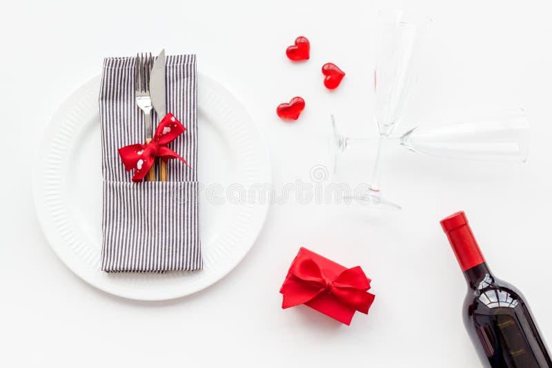 Romantisch diner op de Dag van Valentine Verfraaide schotels, vaatwerk, wijn en giftdoos op witte hoogste mening als achtergrond stock foto's