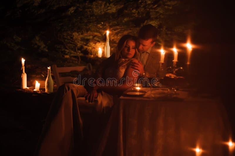 Romantisch diner van een jong paar door kaarslicht in de bergen royalty-vrije stock afbeelding