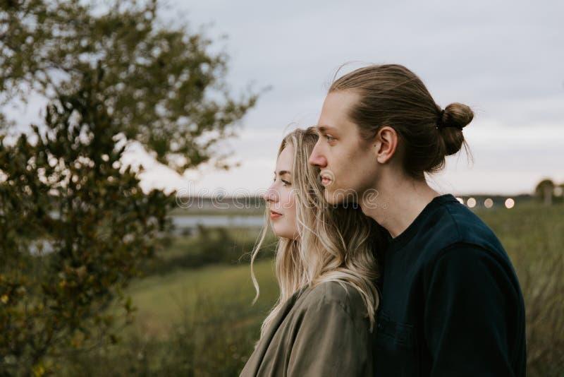 Romantisch en Houdend van Jong Volwassen Paar bij het Park dat Aard bekijkt en de Horizon voor Portretbeelden royalty-vrije stock afbeelding