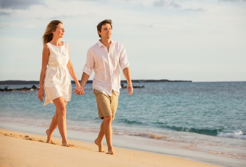 Romantisch gelukkig paar dat op strand bij zonsondergang loopt stock foto