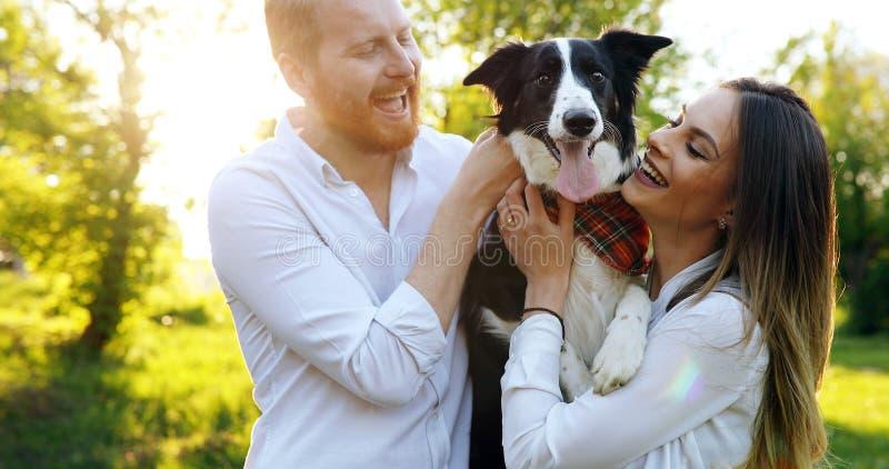 Romantisch gelukkig paar die in liefde van hun tijd met huisdieren in aard genieten stock fotografie