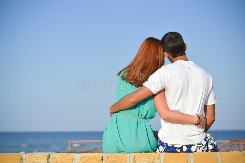 Romantisch gelukkig paar die op zee zitting op zandig strand en het omhelzen kijken royalty-vrije stock fotografie