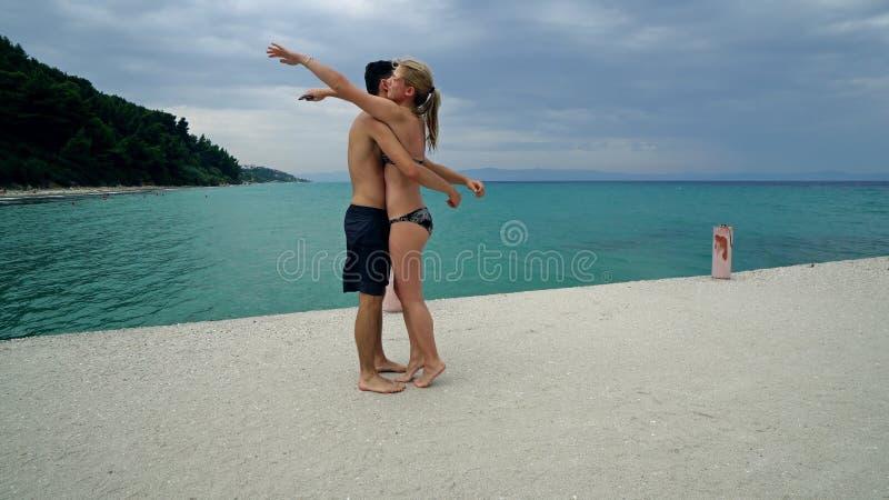 Romantisch gelukkig paar die pret hebben die op strand dansen stock afbeelding