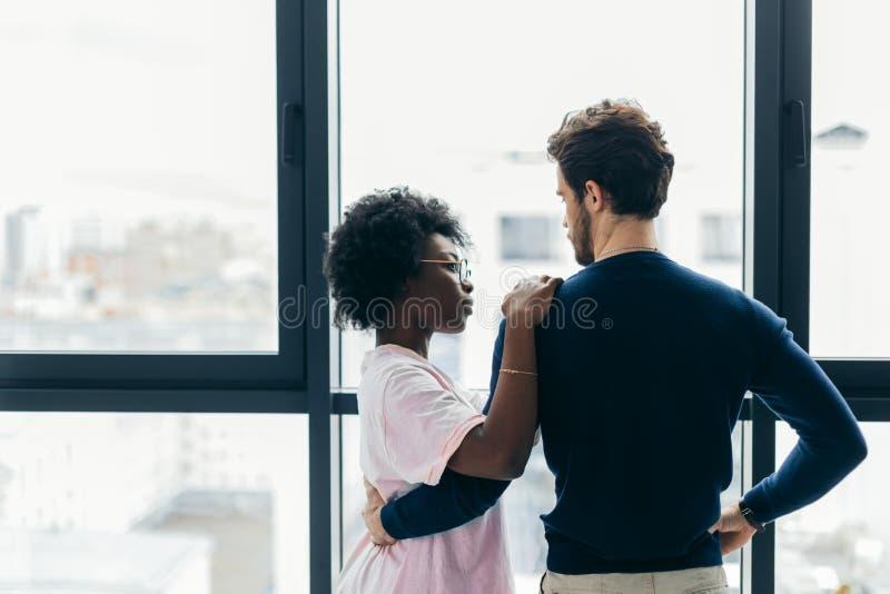 Romantisch gemengd raspaar die zich door het venster bevinden die over hun toekomst denken stock foto's