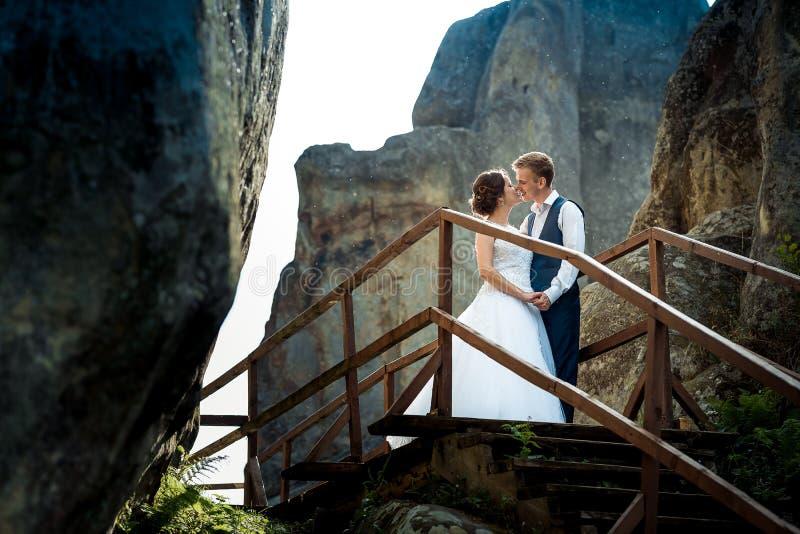 Romantisch gevoelig portret van de jonggehuwden die handen houden en gaan kussen op de houten treden tussen rotsen tijdens royalty-vrije stock afbeelding