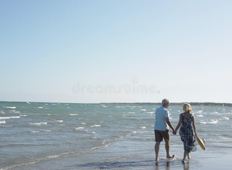 Romantisch Hoger Paar dat op Strand loopt royalty-vrije stock fotografie
