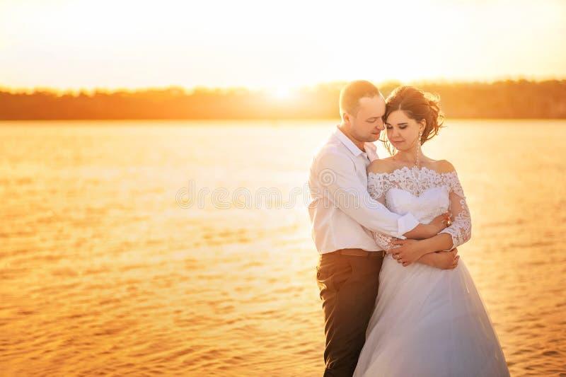 Romantisch huwelijkspaar bij zonsondergang op de kust De bruid en de bruidegom op het strand bij zonsondergang in de zomer royalty-vrije stock foto