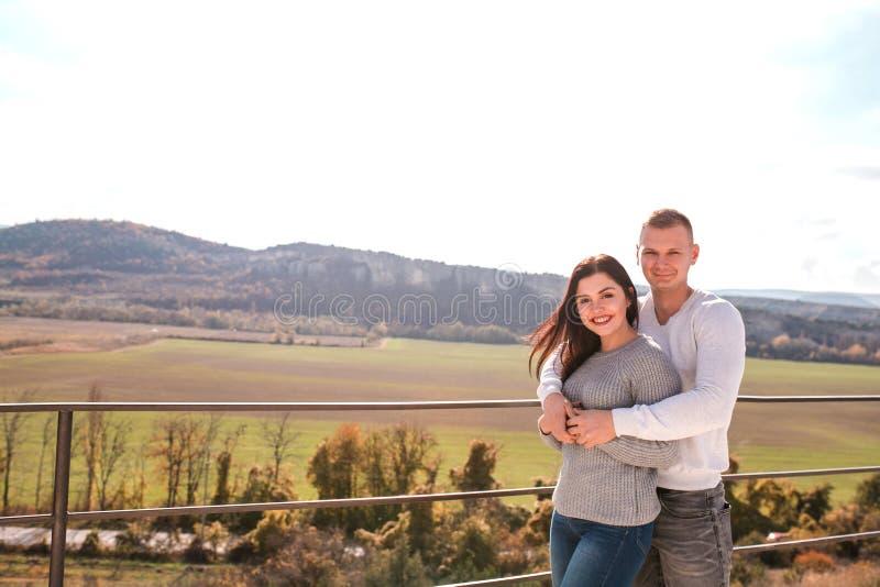 Romantisch jong en paar die in openlucht koesteren glimlachen stock foto's