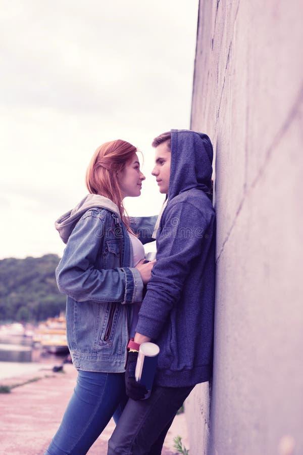 Romantisch jong paar die hun gevoel uitdrukken terwijl het koesteren dichtbij de muur royalty-vrije stock foto