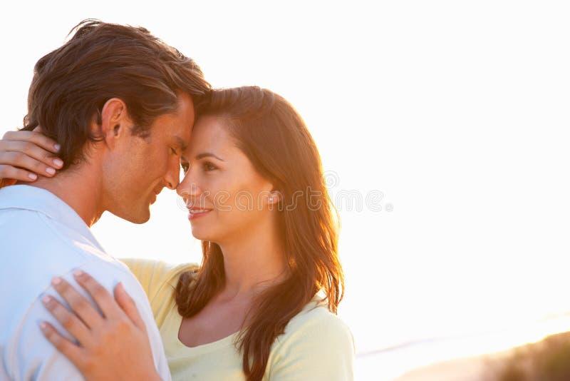 Romantisch Jong paar in liefde bij zonsondergang