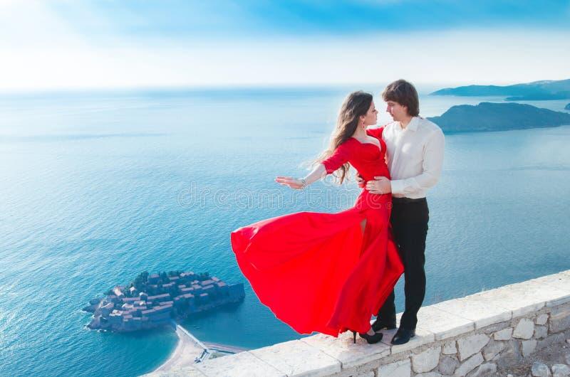 Romantisch jong paar in liefde Het model van het maniermeisje in het blazen rood stock foto