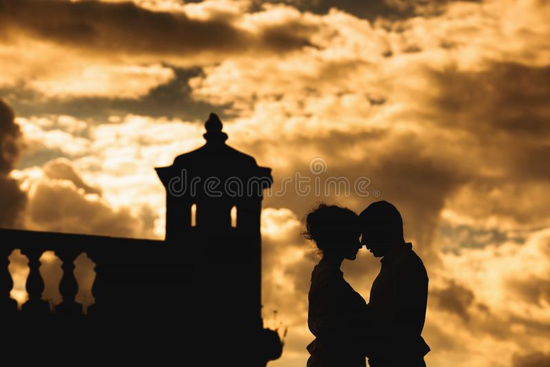 Romantisch jong paar op de vestingsmuur bij zonsondergang stock foto's