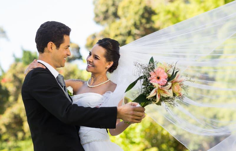 Romantisch jonggehuwdepaar die in park dansen royalty-vrije stock afbeelding