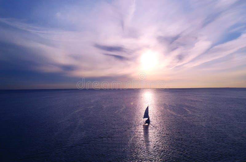 Romantisch kader: jacht die weg in de afstand naar de horizon in de stralen van de het plaatsen zon drijven Purper-roze zonsonder stock foto's