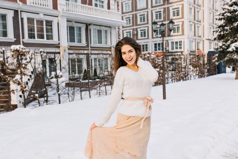 Romantisch langharig meisje in rok het stellen op het straathoogtepunt van sneeuw met lantaarn op achtergrond Openluchtportret va stock afbeeldingen