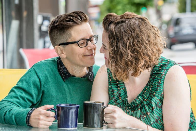 Romantisch lesbisch paar bij bistro in openlucht stock foto's
