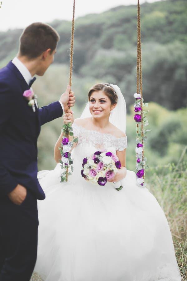 Romantisch, Märchen, glückliche Jungvermähltenpaare, die in einem Park, Bäume im Hintergrund umarmen und küssen stockfotos