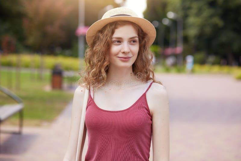 Romantisch meisje die strohoed en de t-shirt van Bourgondië het stellen in park dragen, kijkend opzij glimlachend, enjoing mooie  royalty-vrije stock foto's