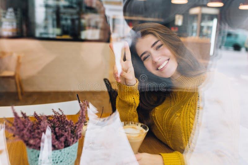 Romantisch meisje in het gebreide cardigan stellen met vredesteken tijdens rust in koffie in koude dag Binnenportret van grappig stock foto's