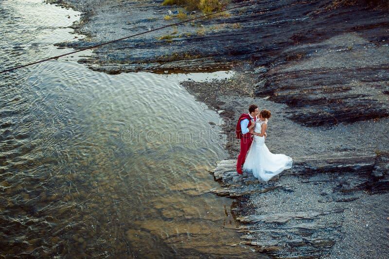 Romantisch openluchtdiehuwelijk van het modieuze jonggehuwdepaar wordt geschoten die bij de rivierbank koesteren Mooi landschap royalty-vrije stock afbeelding