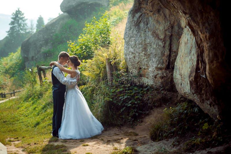 Romantisch openluchthuwelijksportret De modieuze jonggehuwden koesteren en bevinden hoofd-aan-zichhoofd aan elkaar op zonnig stock foto