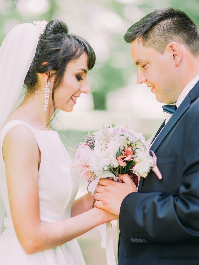 Romantisch openluchtportret van het gelukkige jonggehuwdepaar die het huwelijksboeket van kleurrijke pioenen houden stock foto's