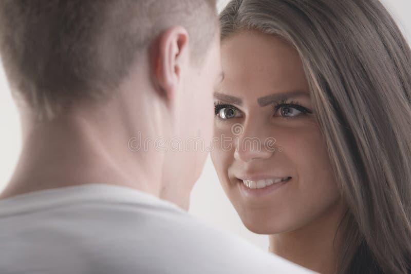 Romantisch paar dat elkaar oog het glimlachen geeft royalty-vrije stock afbeelding