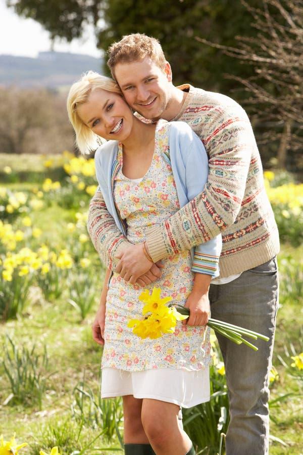 Romantisch Paar dat onder de Gele narcissen van de Lente loopt royalty-vrije stock foto's