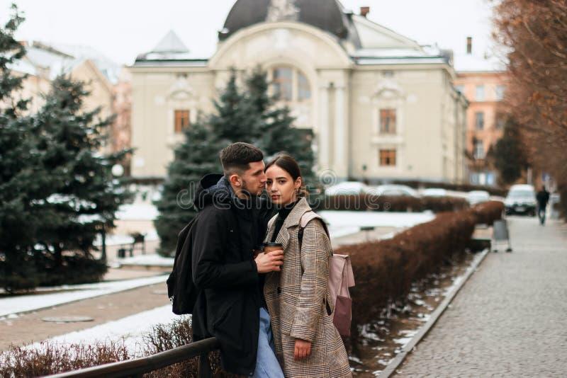 Romantisch paar in de winterdoek het stellen in het stadscentrum stock foto's