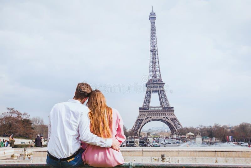 Romantisch paar die de toren van Eiffel in Parijs bekijken stock foto