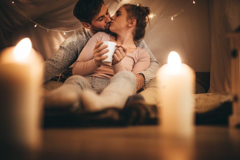 Romantisch paar die elkaar kussen die op bed zitten stock afbeelding