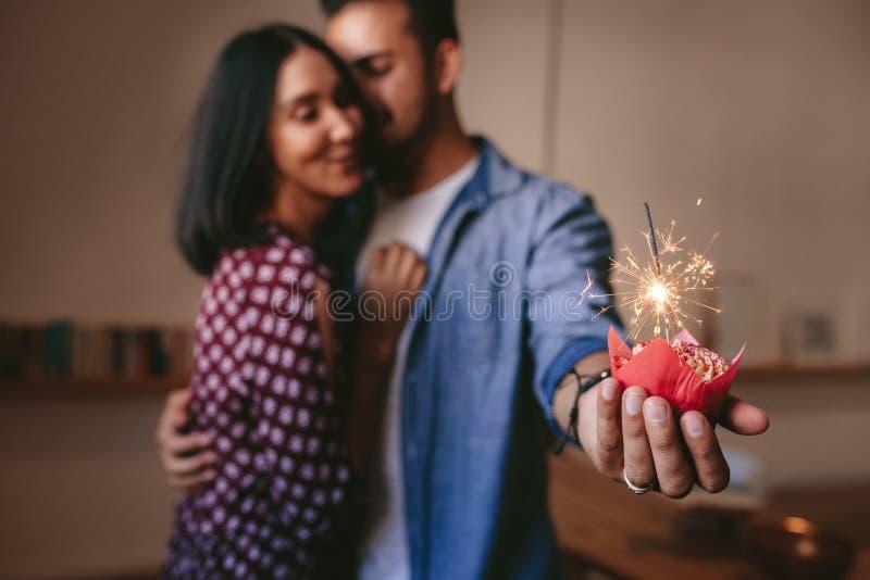 Romantisch paar die hun verjaardag met kopcake vieren stock afbeeldingen