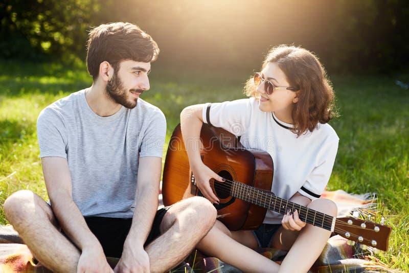 Romantisch paar die in liefde hun tijd doorbrengen die samen bij groen gras zitten die muzikaal instrument spelen Het jonge gebaa stock fotografie