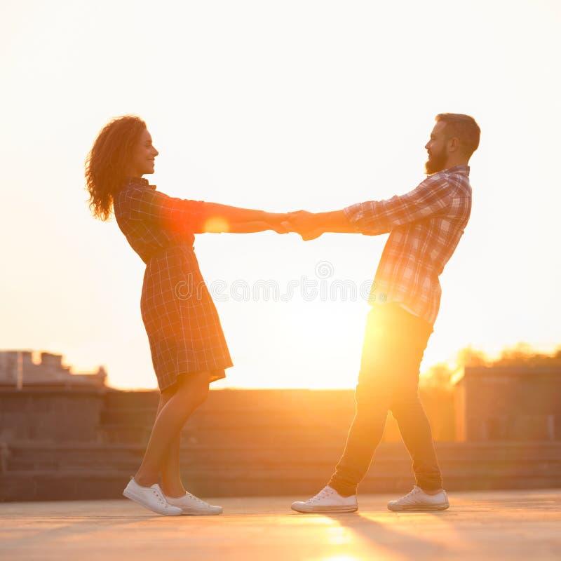 Romantisch paar die pret hebben en bij zonsondergang in de stad dansen royalty-vrije stock foto