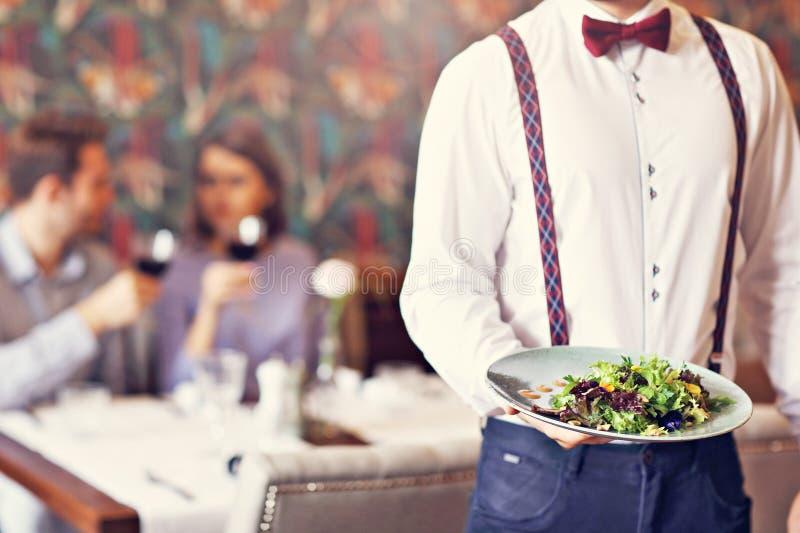 Romantisch paar die in restaurant dateren die door kelner worden gediend royalty-vrije stock foto's