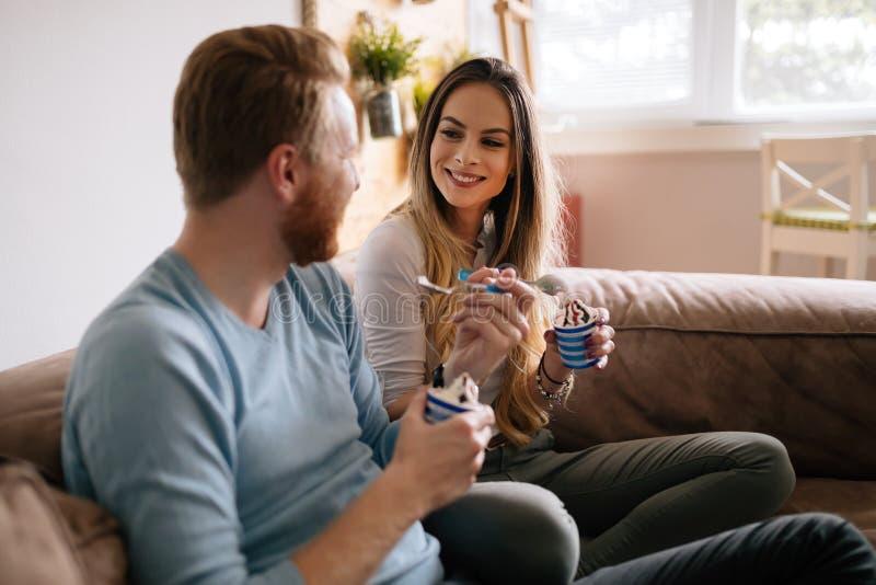Romantisch paar die roomijs samen en het letten op TV eten royalty-vrije stock foto's