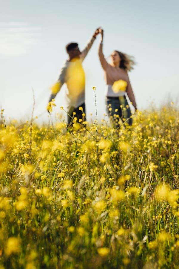 Romantisch paar die in weide van gele bloemen dansen royalty-vrije stock fotografie
