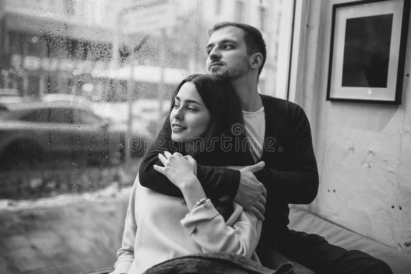 Romantisch paar Het houden van van kerel koestert zijn mooie meisjezitting op de vensterbank in een comfortabele koffie royalty-vrije stock afbeelding